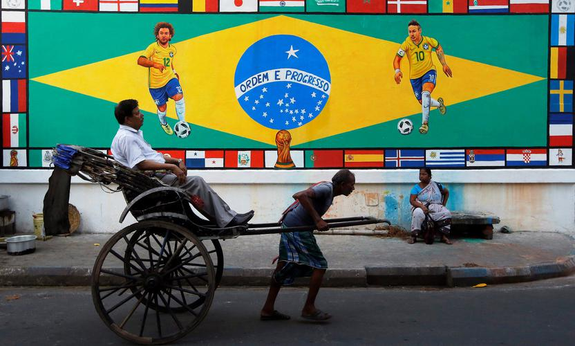 A rickshaw puller in Kolkata, India passes a mural depicting Brazilian football players. The 'Fragile Five' emerging markets economies of Brazil, India, Indonesia, South Africa and Turkey appear on firmer footing than five years ago. REUTERS/Rupak De Chowdhuri