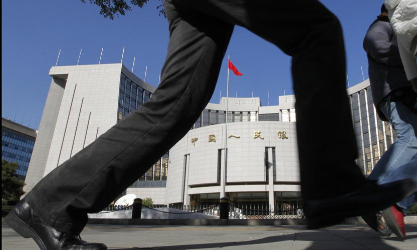 A pedestrian walks past the headquarters of the People's Bank of China, the central bank, in Beijing. REUTERS/Grace Liang