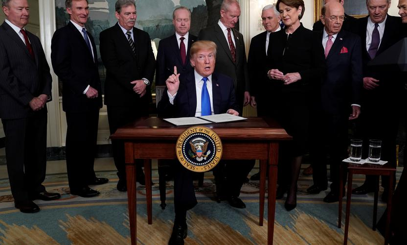 U.S. President Donald Trump, surrounded by business leaders and administration officials, prepares to sign a memorandum on intellectual property tariffs on high-tech goods from China, at the White House in Washington, U.S. March 22, 2018.  REUTERS/Jonathan Ernst