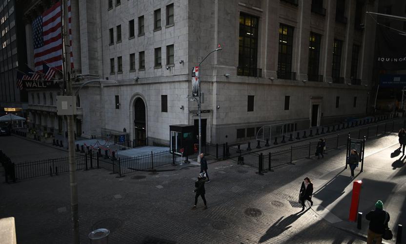People pass the New York Stock Exchange. (Photo by Johannes Eisele/AFP via Getty Images)