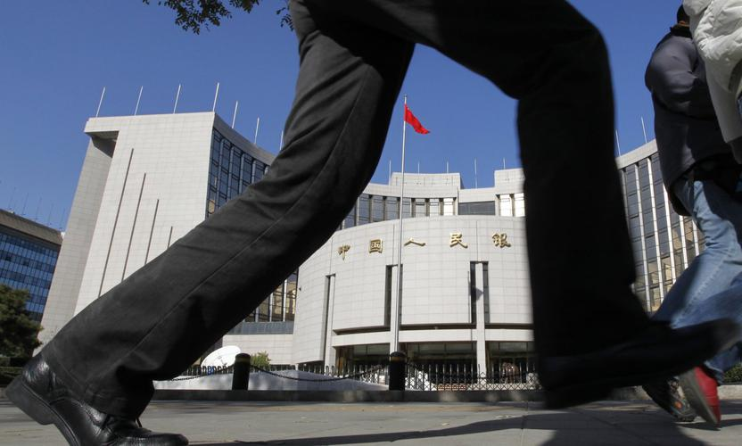 A pedestrian walks past the headquarters of the People's Bank of China, the central bank, in Beijing November 8, 2010. Chinese bond yields rose near a two-year high on Monday in anticipation of consumer price inflation data that is expected to cement the case for more policy tightening. REUTERS/Grace Liang (CHINA - Tags: BUSINESS)